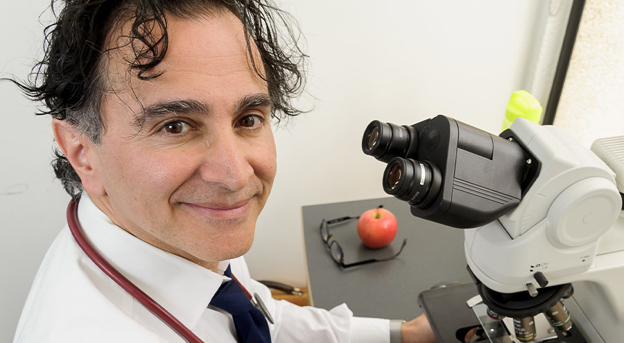 CHÉOS Scientist Dr. Kamran Shojania using a microscope
