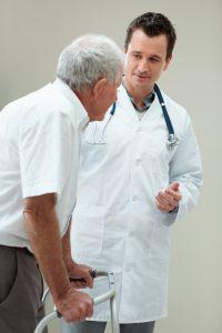 Handsome doctor assisting an old man on a walker
